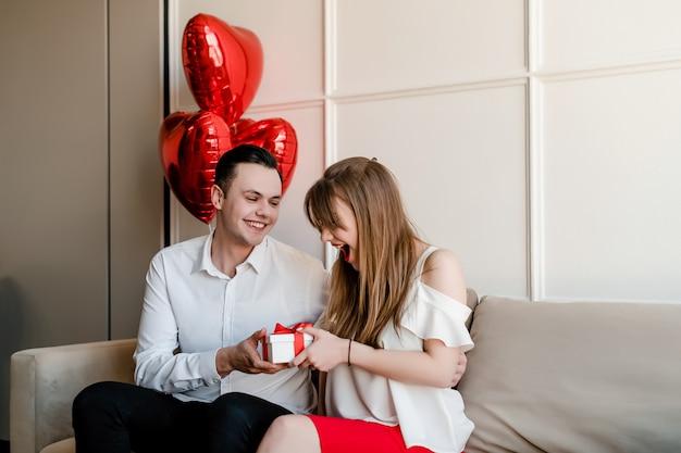 Homem dá presente para mulher sorridente com balões em forma de coração no sofá em casa