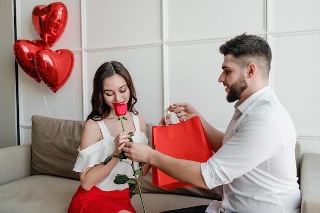 Homem dá sacolas e rosa vermelha para mulher em casa com balões em forma de coração no sofá