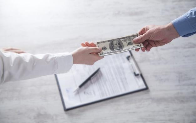 Homem dá suborno a funcionário no escritório. corrupção, suborno
