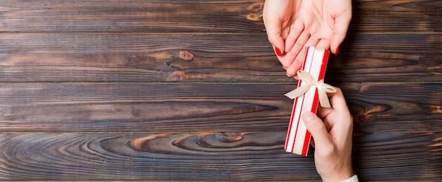 Homem dá uma caixa de presente de natal na mão de uma mulher
