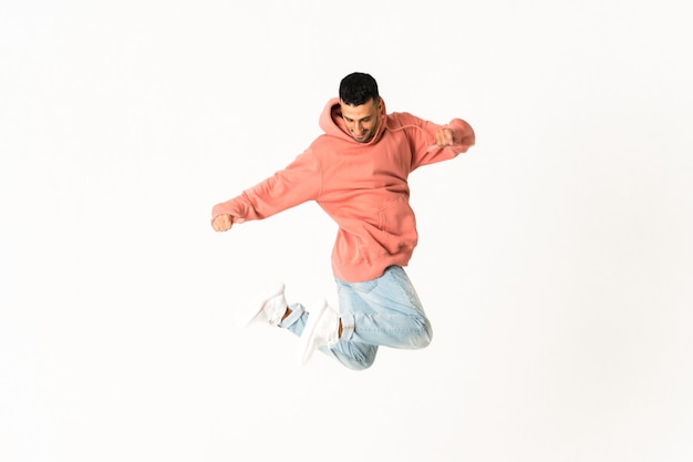 Homem dançando estilo de dança de rua sobre parede branca isolada
