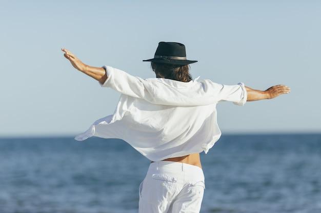 Homem dançando feliz em uma camisa branca e chapéu preto na praia