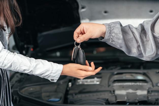 Homem dando a cliente as chaves do carro consertado em uma oficina mecânica