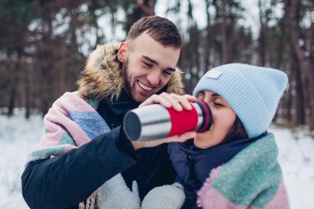 Homem dando a sua namorada chá quente para beber na xícara de garrafa térmica. casal apaixonado andando juntos na floresta de inverno.