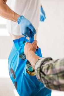 Homem dando a um voluntário uma sacola com doações