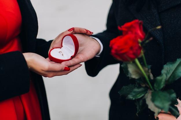 Homem dando anel de noivado para garota