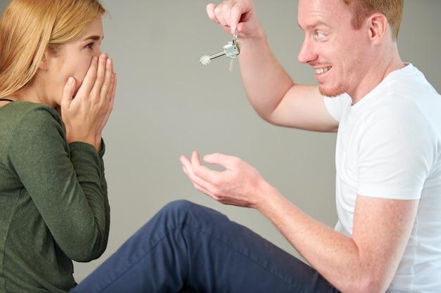 Homem dando as chaves do apartamento para a namorada