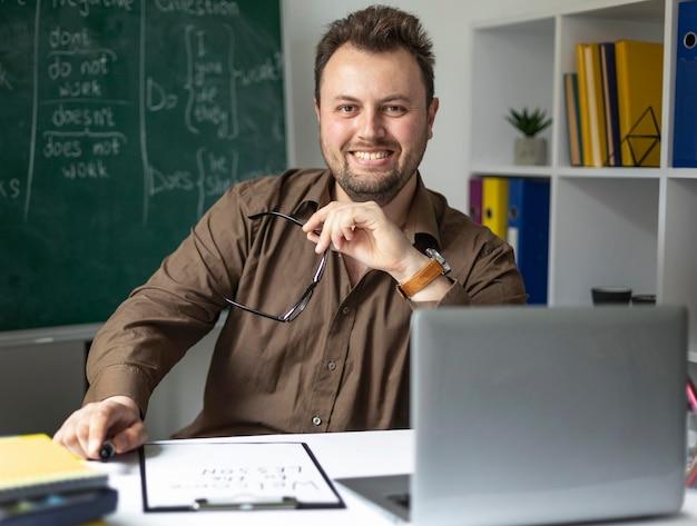 Homem dando aula de inglês online para crianças
