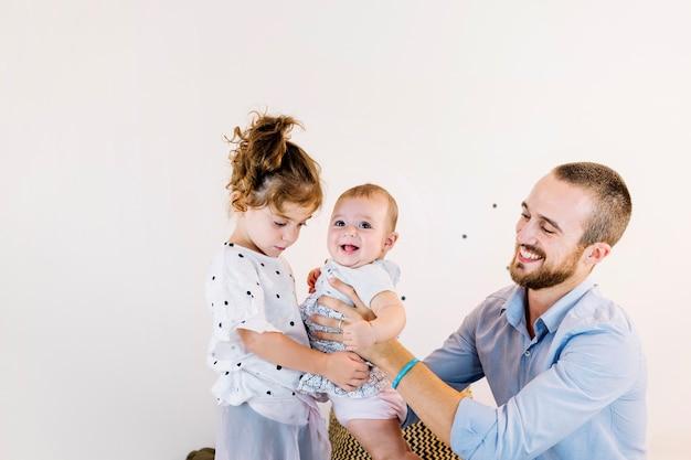 Homem dando bebê para menina