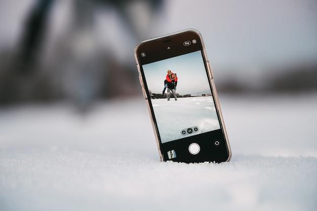 Homem dando carona para a namorada enquanto se divertem juntos e tirando uma selfie com o smartphone colocado na neve no campo de inverno