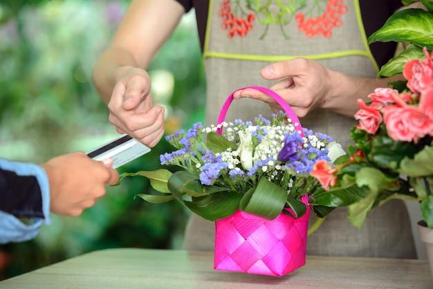 Homem dando cartão de crédito para florista após a compra.