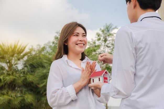 Homem dando casa chave para mulheres conceito de família feliz casal amor negócio familiar aluguel venda seguro investimento