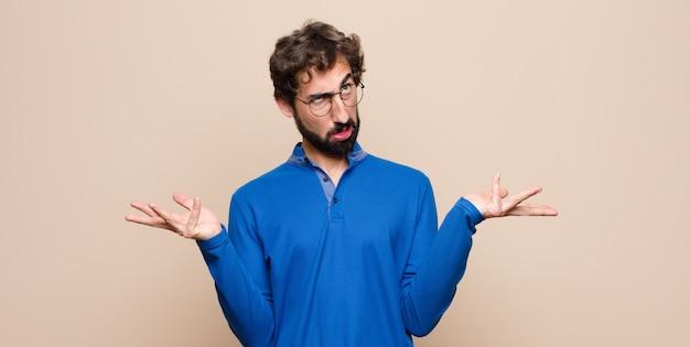 Homem dando de ombros homem com uma expressão idiota, louca, confusa, confusa, sentindo-se irritada e sem noção