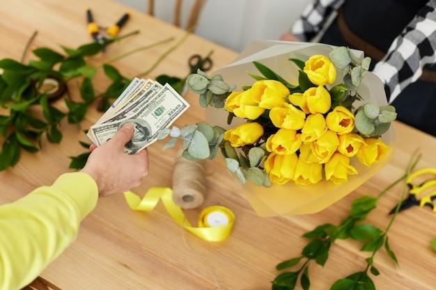 Homem dando dinheiro para flores de pagamento à mulher do florista.