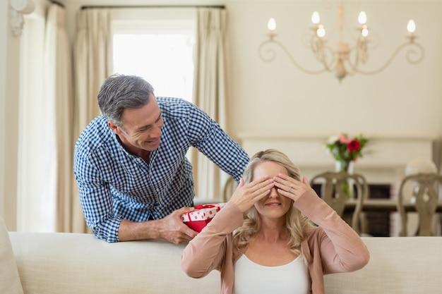 Homem dando presente surpresa para mulher na sala de estar