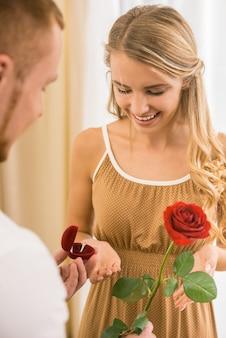 Homem dando rosa e anel de casamento para sua linda namorada