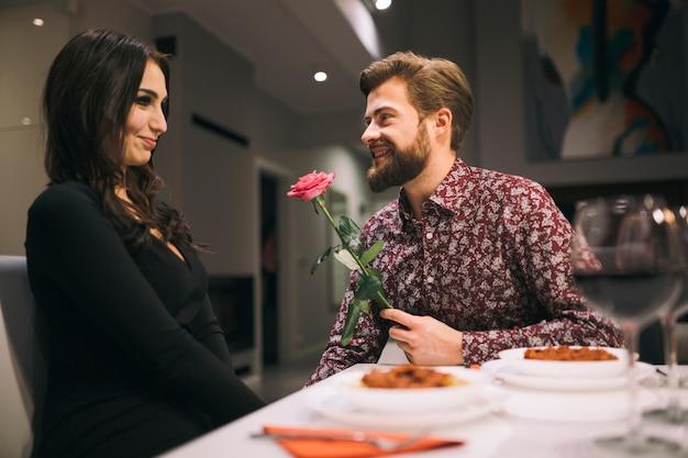 Homem dando rosa para garota no café