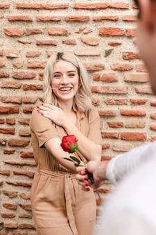 Homem dando rosa para mulher feliz