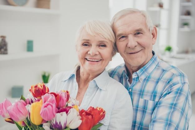Homem dando um buquê de flores para sua esposa