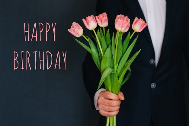 Homem dando um buquê de tulipas flores cor de rosa. cartão com feliz aniversário texto