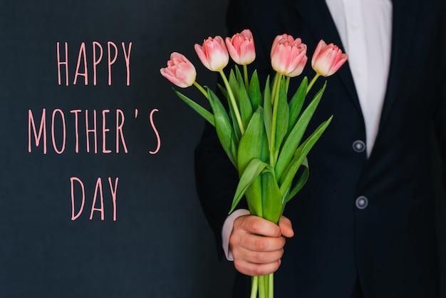 Homem dando um buquê de tulipas flores cor de rosa. cartão com texto feliz dia das mães