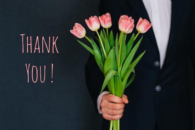 Homem dando um buquê de tulipas flores cor de rosa. cartão com texto obrigado
