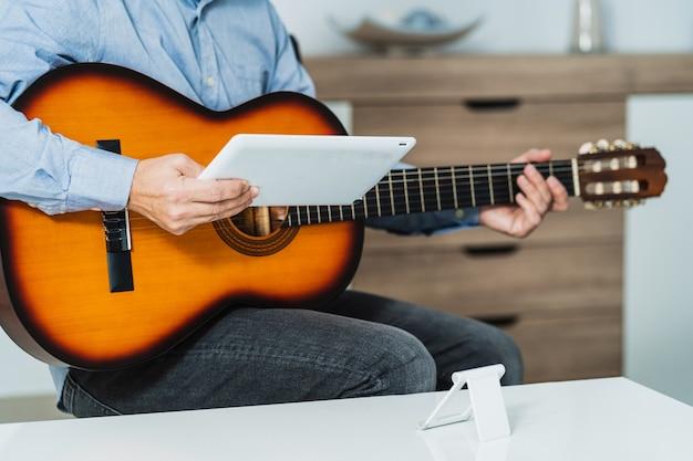 Homem dando uma aula de violão online com o tablet, ele está revisando a aula