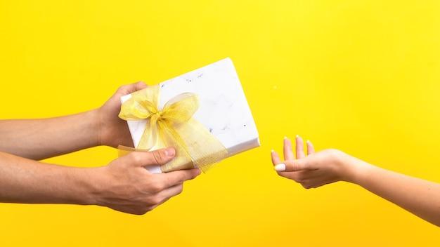 Homem dando uma caixa de presente com fita vermelha para uma mulher