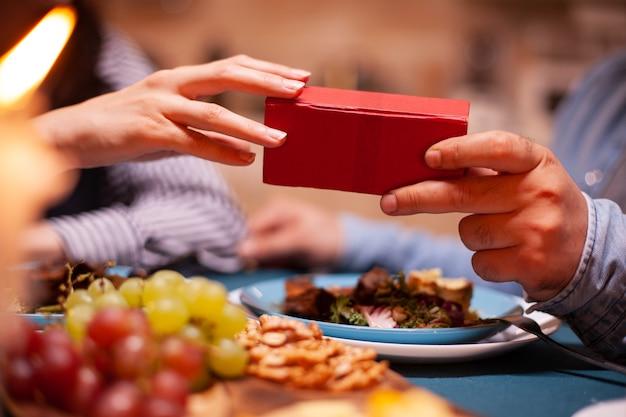 Homem dando uma caixa de presente para a esposa e jantando juntos