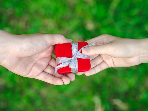 Homem dando uma caixa de presente vermelha para mulher.