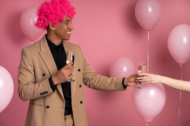 Homem dando uma taça de champanhe para um amigo