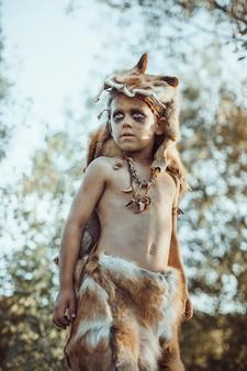 Homem das cavernas, menino viril ao ar livre. antigo guerreiro pré-histórico.