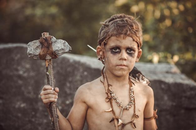 Homem das cavernas, menino viril com arma primitiva caça ao ar livre.