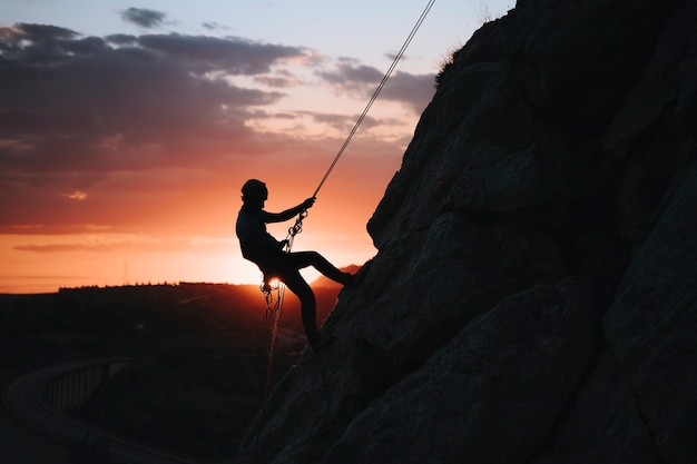 Homem de 30 anos escalando uma montanha ao pôr do sol