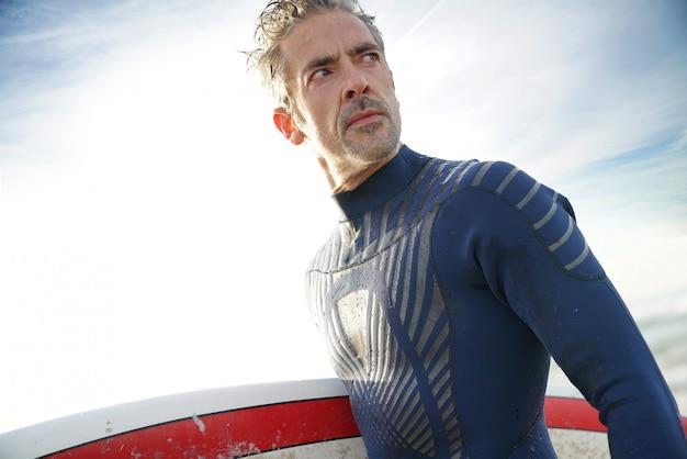 Homem de 40 anos de idade com prancha de surf na praia