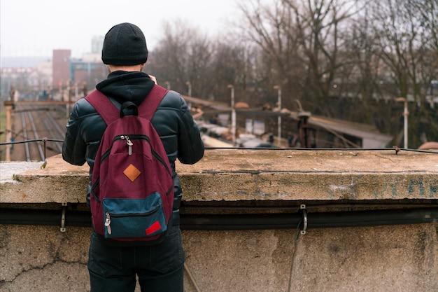 Homem de agasalho preto e mochila borgonha fica na ponte e olhando para um trem. estação de trem. masculino. pensando. estrada de ferro. vida. decisão. calma. pensamentos. andar. viagem
