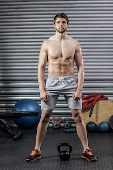 Homem de ajuste sem camisa posando no ginásio crossfit