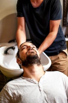 Homem de alta vista, recebendo uma lavagem de cabelo