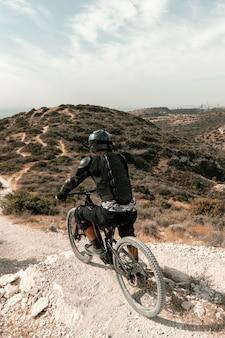 Homem de alto ângulo andando de mountain bike