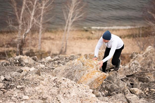 Homem de alto ângulo caminhando sobre pedras