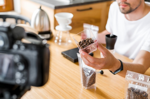 Homem de alto ângulo com grãos de café