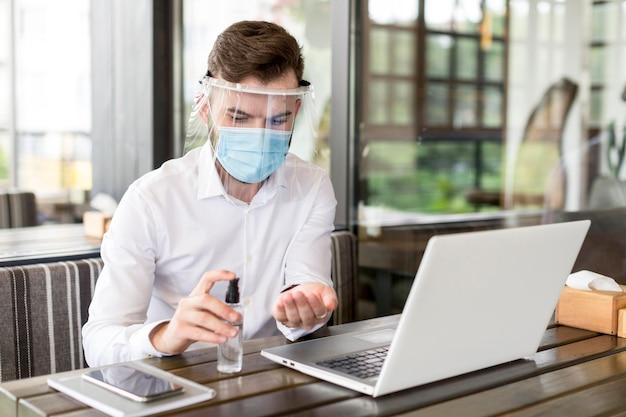 Homem de alto ângulo com máscara trabalhando no laptop