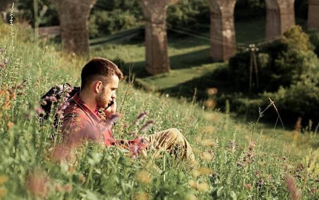 Homem de alto ângulo em campo verde, falando por telefone