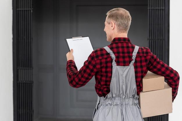 Homem de alto ângulo, entregando o pacote