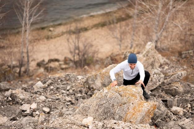 Homem de alto ângulo escalando rochas