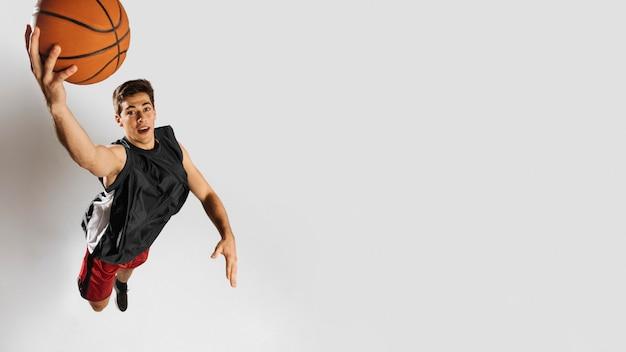 Homem de alto ângulo jogando basquete com espaço de cópia