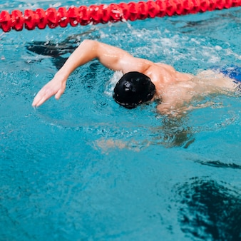 Homem de alto ângulo nadando com o rosto na água