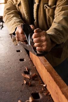 Homem de alto ângulo polindo madeira