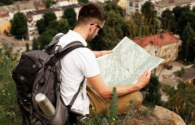 Homem de alto ângulo, viajando sozinho lendo o mapa