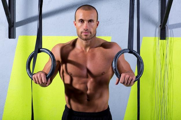 Homem de anel de mergulho crossfit relaxado depois de treino no ginásio
